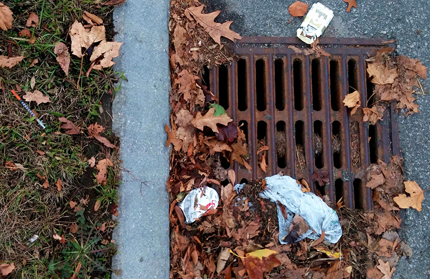A cigarette box, beer can and a hypodermic needle are just three of the littered items threatening to clog and pollute this storm drain on an entrance ramp to I-195 near India Point Park in Providence. Each is a commonly littered item, according to representatives of southern New England's departments of transportation. (Kevin Proft/ecoRI News photos)