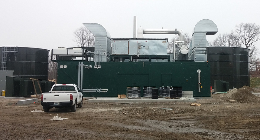 Generators will turn the methane into electricity, and excess heat from the generators will be used to maintain the proper temperature of the digesters. The black tanks in the background are the wastewater treatment tanks.