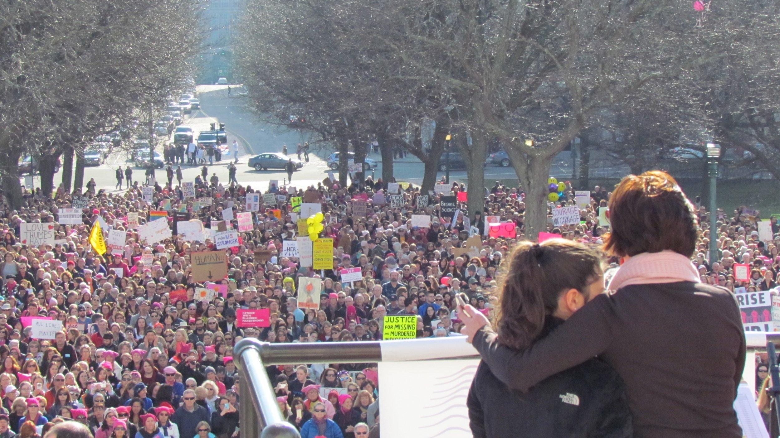 Gov. Gina Raimondo hugs daughter Ceci during the Jan. 21 Rally for Women's Solidarity at the Rhode Island Statehouse. (Tim Faulkner/ecoRI News photos)