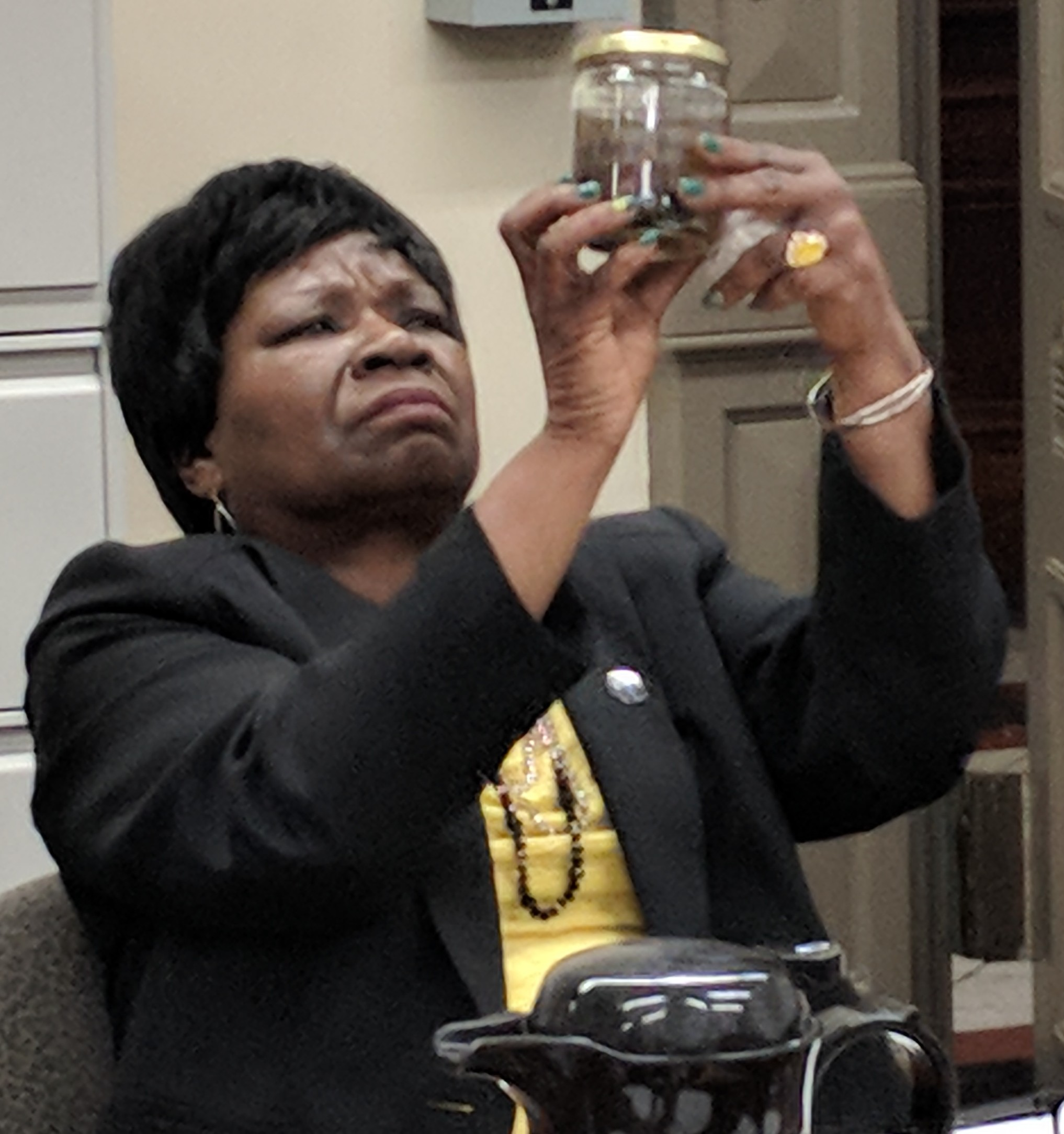 Providence City Council member Mary Kay Harris examines a jar of microplastics taken from the Providence River. (Tim Faulkner/ecoRI News)