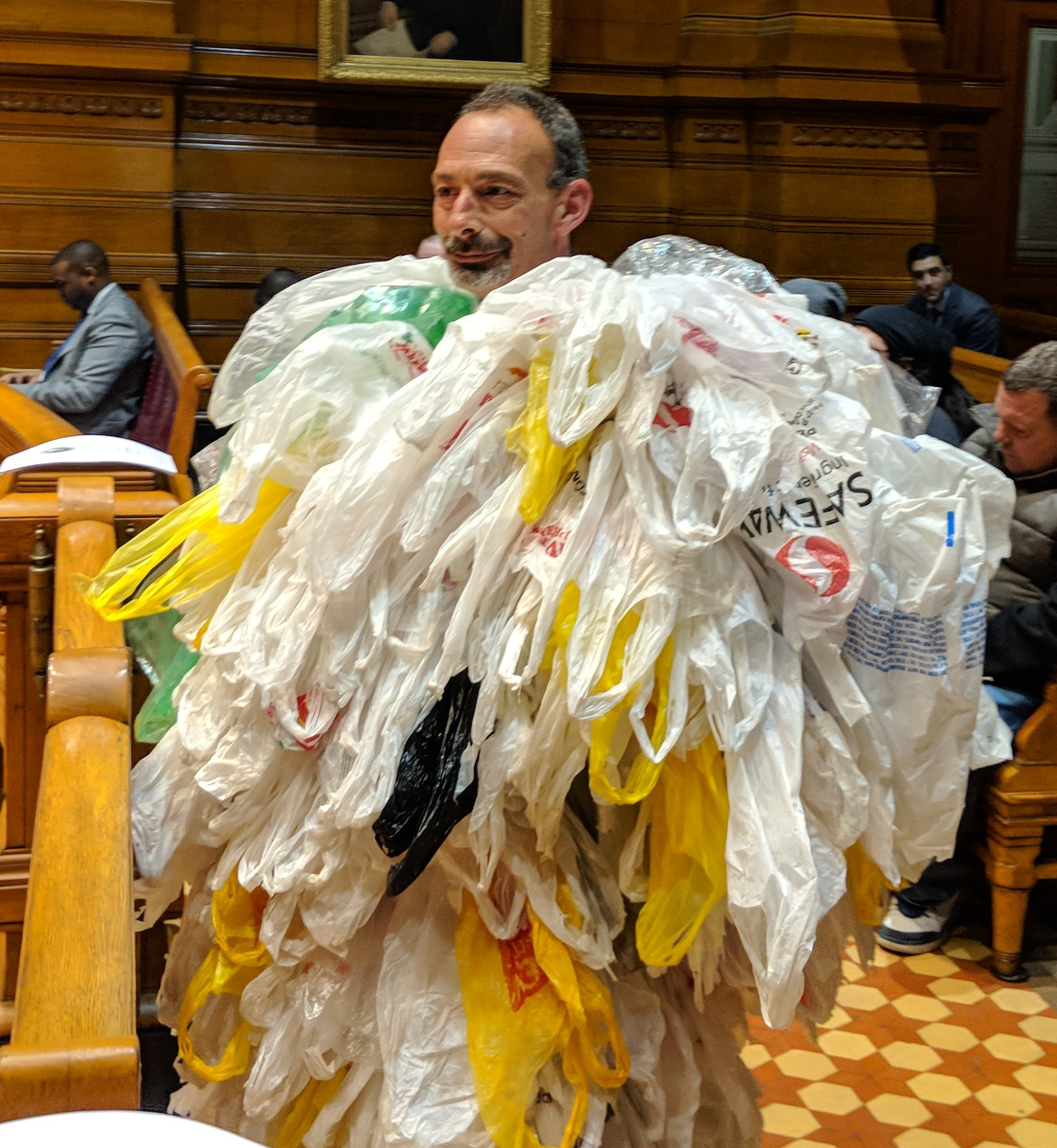 At the Providence City Council's March 1 meeting, Lou Perrotti, director of conservation programs at Roger Williams Park Zoo, wore a suit of plastic bags in support of the ban. (Tim Faulkner/ecoRI News)