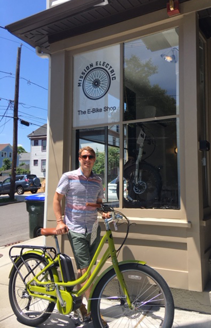 Mission Electric owner Tyler Justin with a Populo in front of his shop on the corner of Ives and Power in Providence. (Nicholas Boke/ecoRI News)