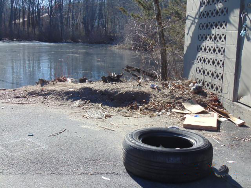 A Dumpster on the grounds of the Apartments at Remington Pond in West Warwick, R.I., is close to the water and carelessly filled. (Courtesy photos)
