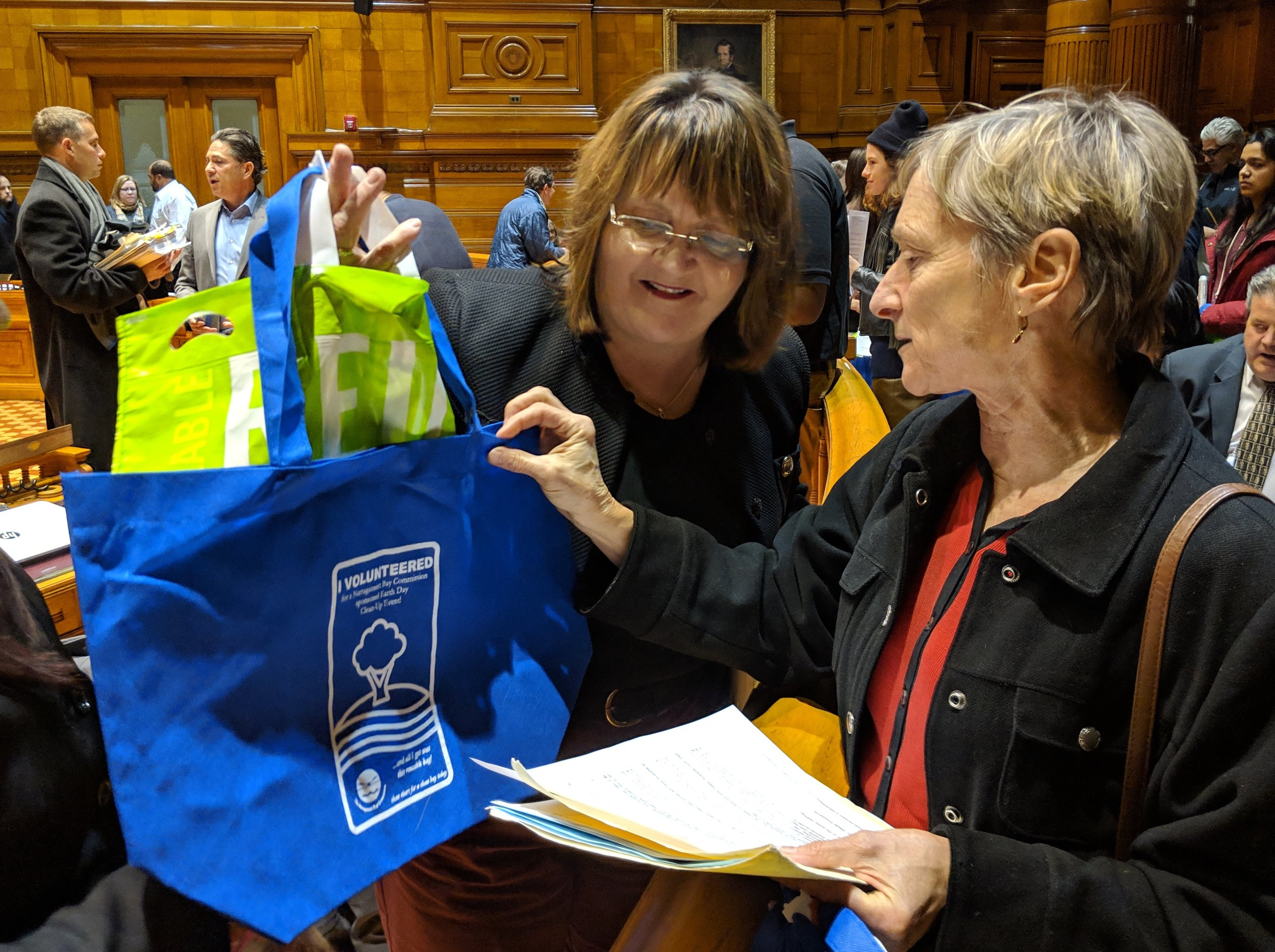Debbie Schimberg, right, of Zero Waste Providence delivers reusable bags to Providence City Council member Jo-Ann Ryan. (Tim Faulkner/ecoRI News photos)
