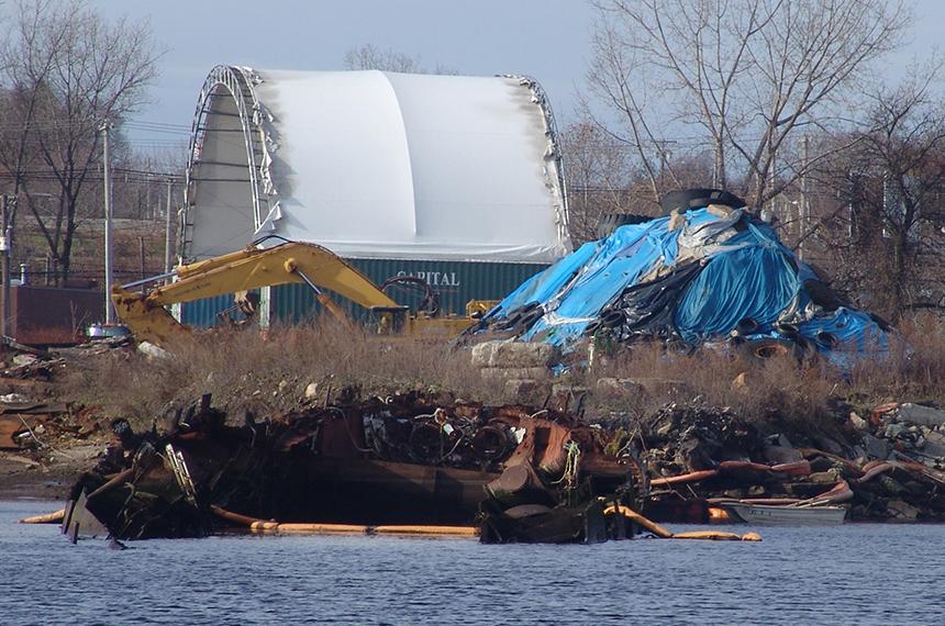 A blue tarp on the property of Rhode Island Recycled Metals on the Providence waterfront covers a mound of sediment that the business illegally dredged when it envisioned pulling a Russian submarine to shore to be scrapped. That mound likely contains some nasty stuff. (Frank Carini/ecoRI News)