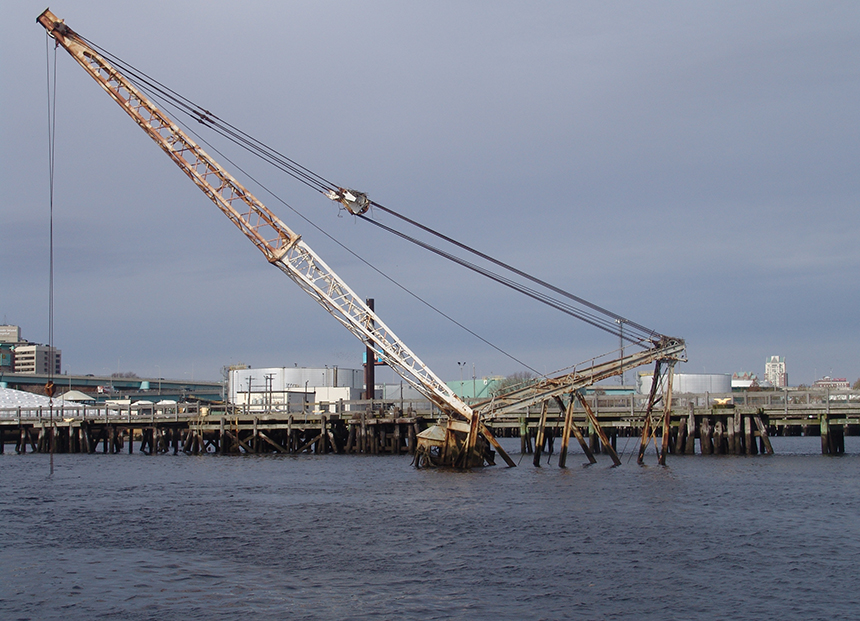 This floating crane owned by an East Providence man sank in the Providence River a year ago. The barge was leaking oil and the owner was cited for violating five pollution laws. But nothing has been done. (Frank Carini/ecoRI News)