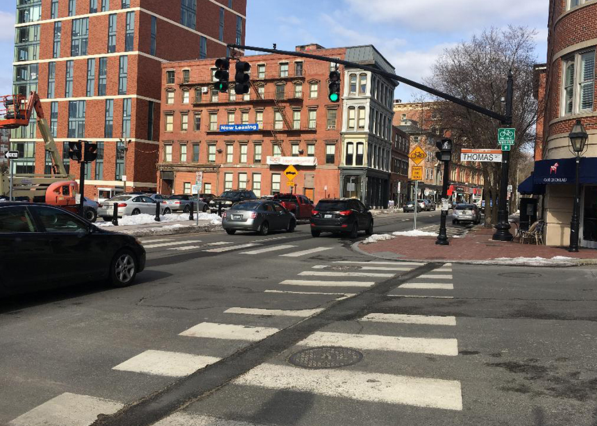 This stretch of North Main Street in Providence features two signs promoting bicycling, but with two traffic lanes and parking on both sides there's not much room left for bikes. (Joanna Detz/ecoRI News photos)