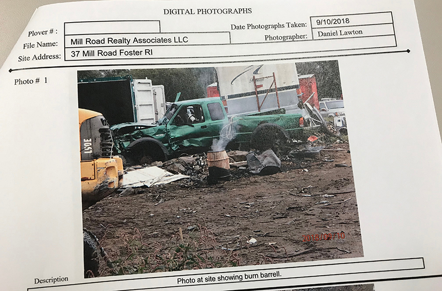 A DEM inspector took this photo last year during a visit to the Foster salvage yard. He found some 2,000 vehicles in varying states of disrepair and evidence that solid waste was openly being burned, as a smoldering burn barrel holding an oil filter and ash was found. (Frank Carini/ecoRI News)
