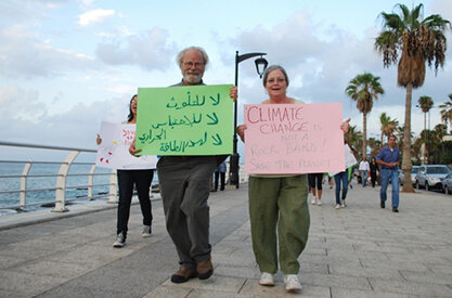 "About 10 years ago the author and his wife, Buffy, joined students for a cleanup in Beirut. Nick's sign reads: 'Don't pollute, no [global] warming, don't waste energy.' Buffy's student-made sign reads: '""Climate Change: It's Not a Rock Band — Save the Planet.' (Courtesy photo)"