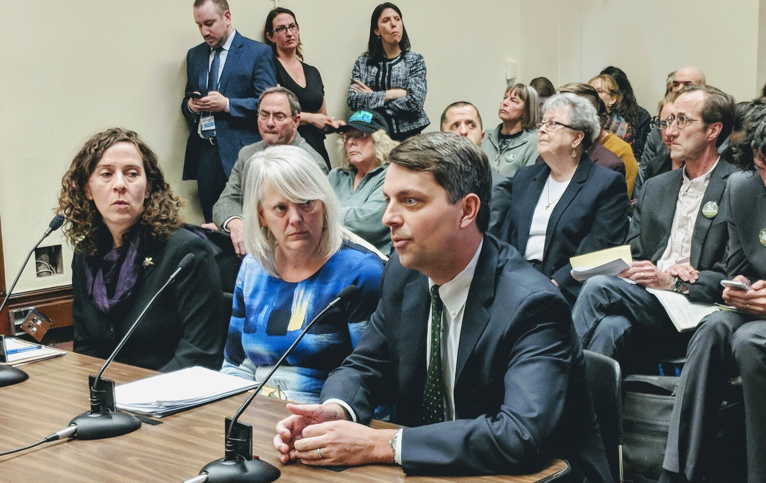 Rep. Christopher Blazejewski, right, D-Providence, sponsored the Act on Climate 2020 House bill. He spoke at the March 5 hearing before the House Committee on the Environment and Natural Resources. DEM director Janet Coit, center, and Amy Moses of the Conservation Law Foundation sit with him. (Tim Faulkner/ecoRI News staff)