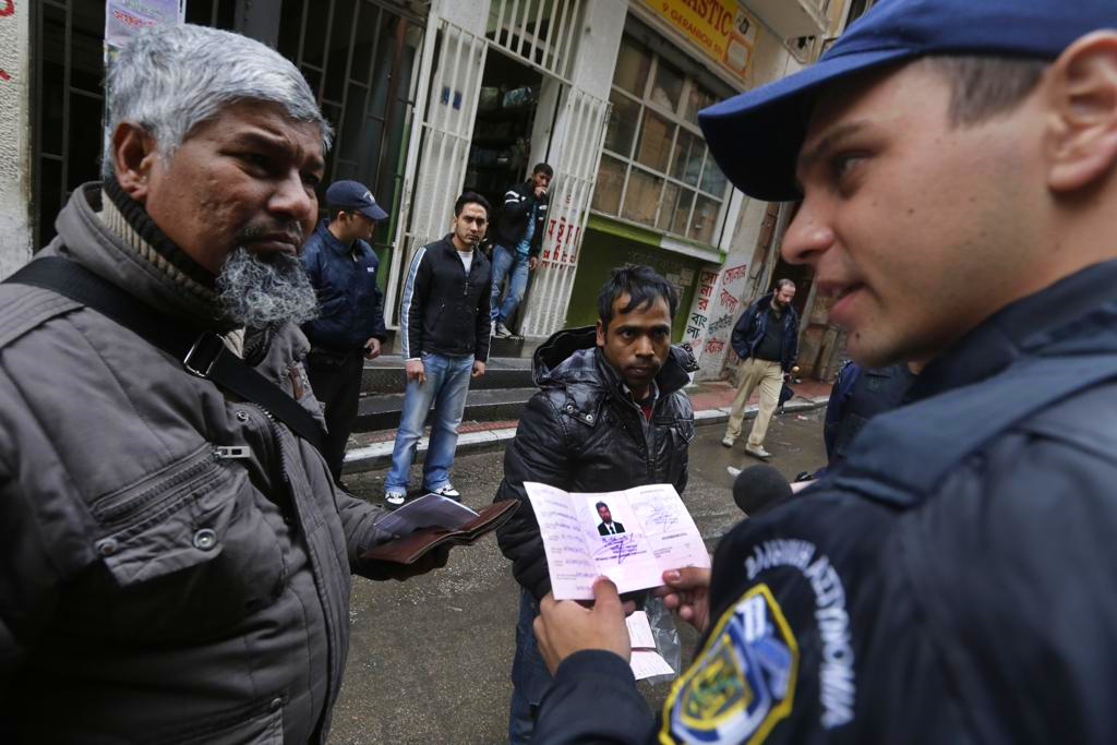 Greek police check the papers of refugees.
