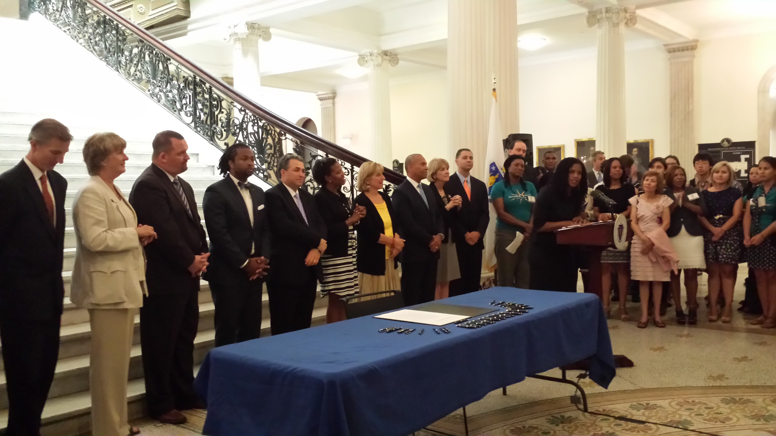 Lydia Edwards (speaking) and other coalition membersat the signing of the Domestic Workers Bill of Rights(Governor Patrick to Lydia's right)