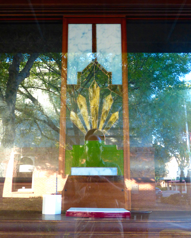 My reflection from a store window in oroville, california angled to appear as if I wear the stained glass feathered headress, which has five feathers for the five core beliefs.