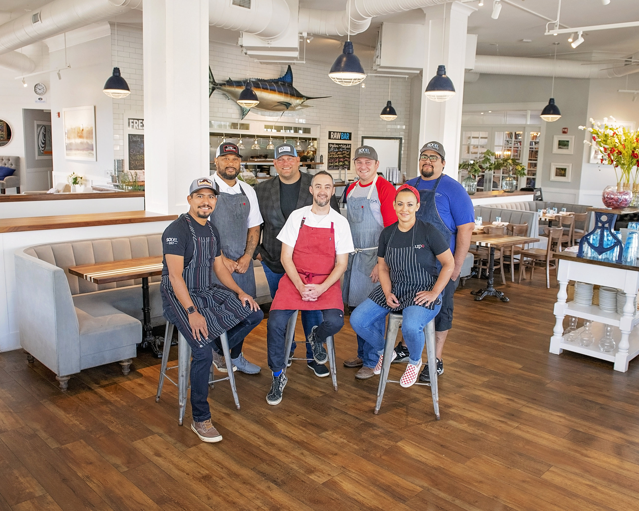 Chris Parks (center), a SoDel Concepts employee since 2014, was recently promoted to the position of corporate chef.Here, he is surrounded by SoDel Concepts teammates. From left to right: Chef Efrain Martinez; Maurice Catlett, corporate chef; Scott Kammerer, president; Ronnie Burkle, corporate chef; Chef Raul Rodriguez; and Chef Nina Maddox.