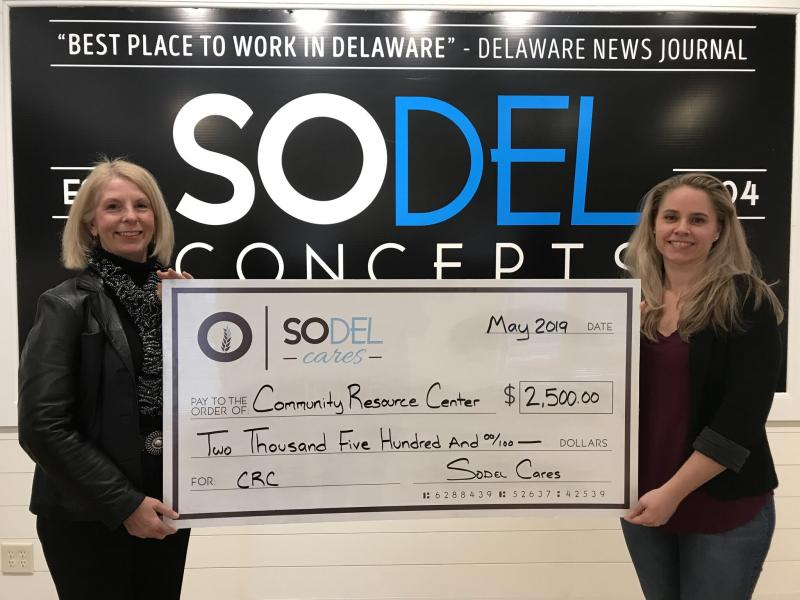 Community Resource Center Director Jo Allegro-Smith, left, accepts the $2,500 donation check from Lindsey Barry, SoDel Concepts controller. SUBMITTED PHOTO