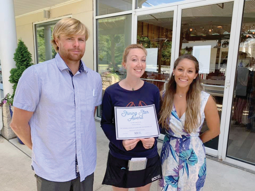 Managers Colin Herlihy and Danae Evans of NorthEast Seafood Kitchen in Ocean View present a Shining Star Award to Victoria Rioux (center).  Coastal Point • Submitted