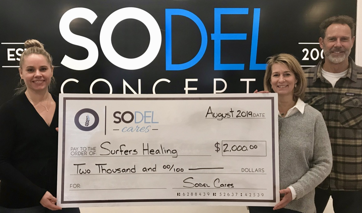 SoDel Cares, the philanthropic arm of SoDel Concepts, recently donated $2,000 to Surfers Healing, which uses surfing to enrich the lives of people with autism. Lindsey Barry, controller for SoDel Concepts, presents the check to Kelly and Dale Loeser, the owners of Quiet Storm, who help coordinate local Surfers Healing activities.
