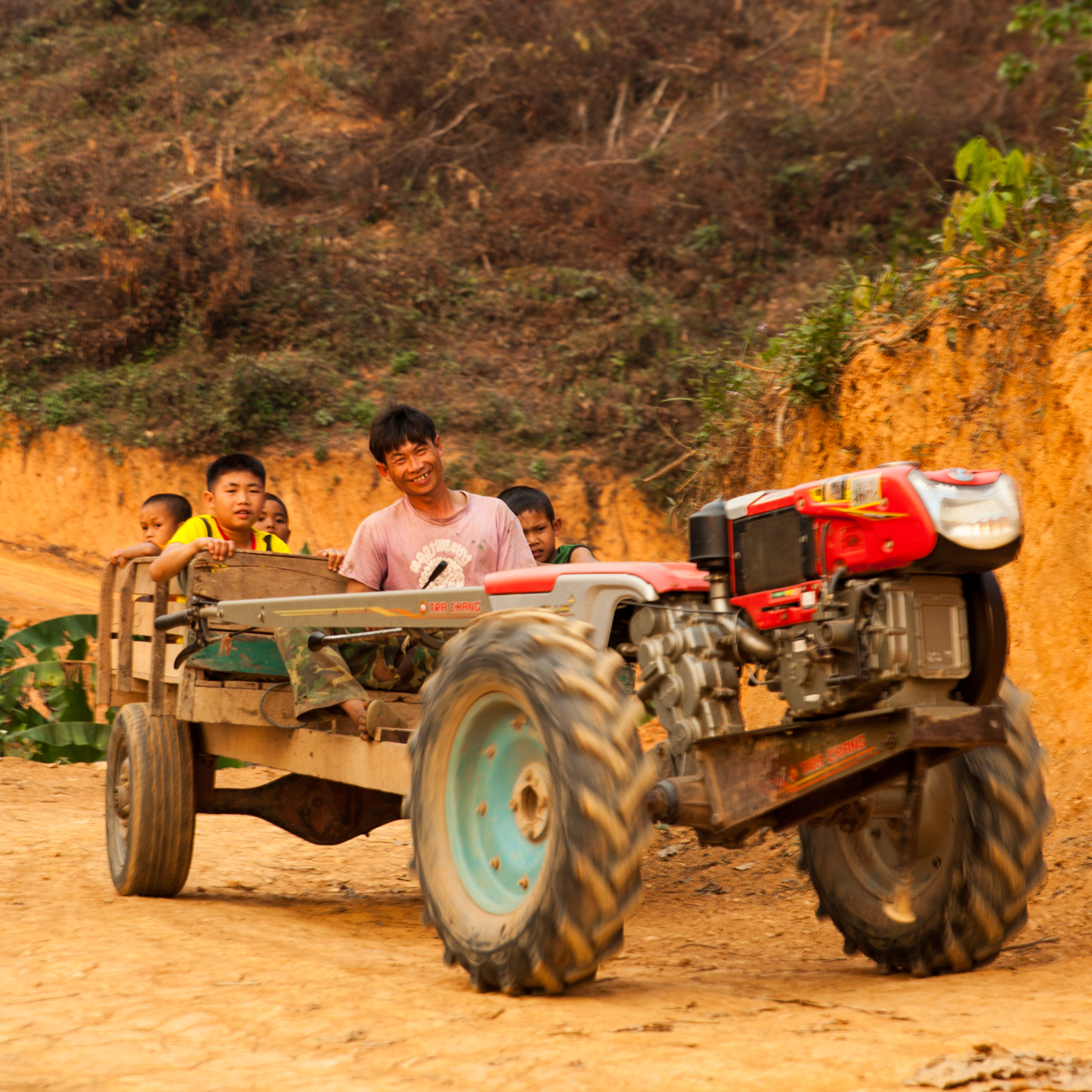 "Some friendly people out on the trail.  This is the most literal translation of a ""horseless carriage"" I have ever encountered.  They were common throughout northern Laos."