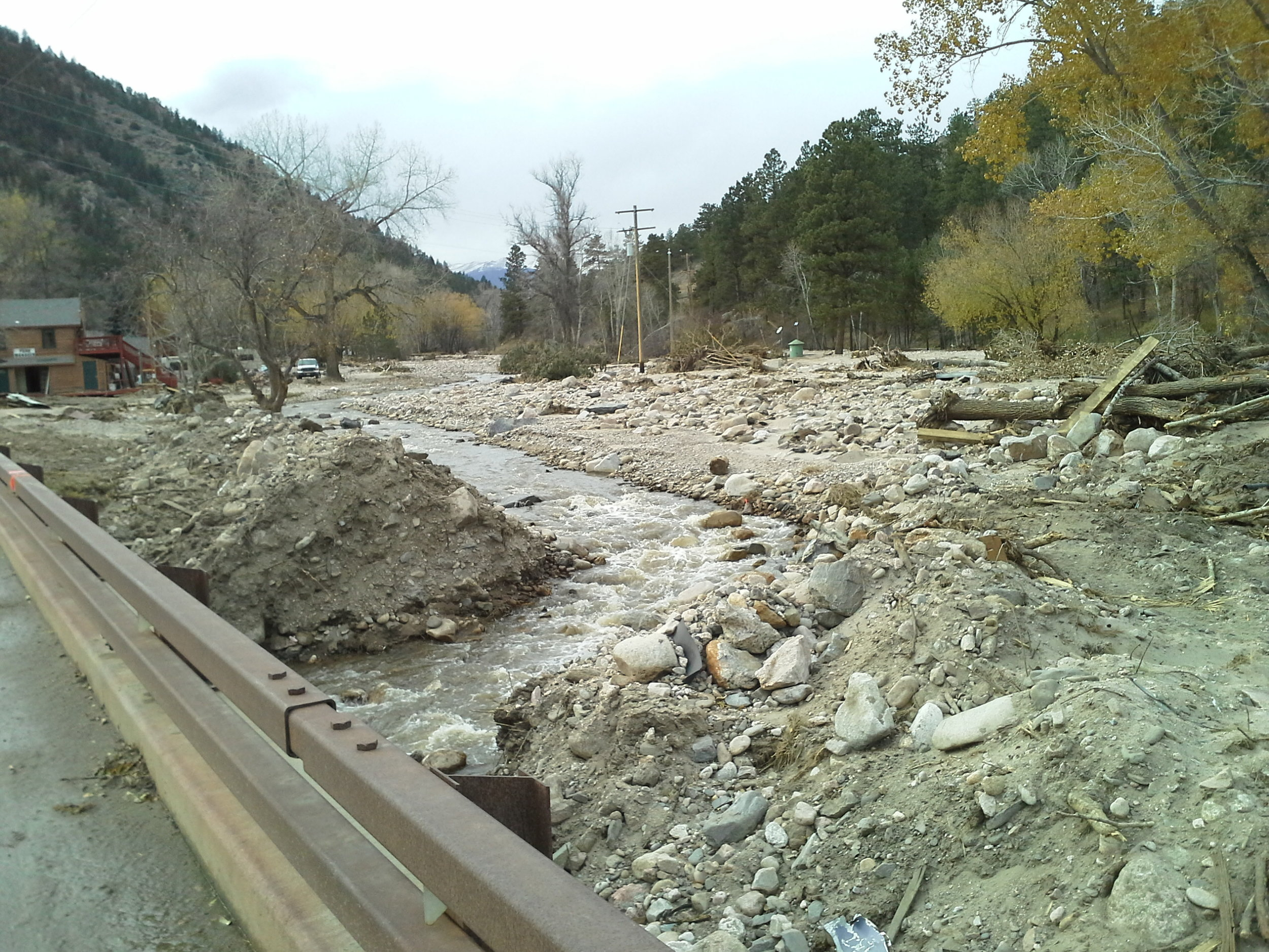 November 2013: Looking upstream at the North Fork of the Big Thompson River from the US 34 bridge 2 months after the flood. The flood deposited massive amounts of sediment and debris at the confluence of the two rivers. Water and sediment caused damage the homes, businesses, roadways, and bridges located in the active river corridor. Photo Credit: Bill Spitz.