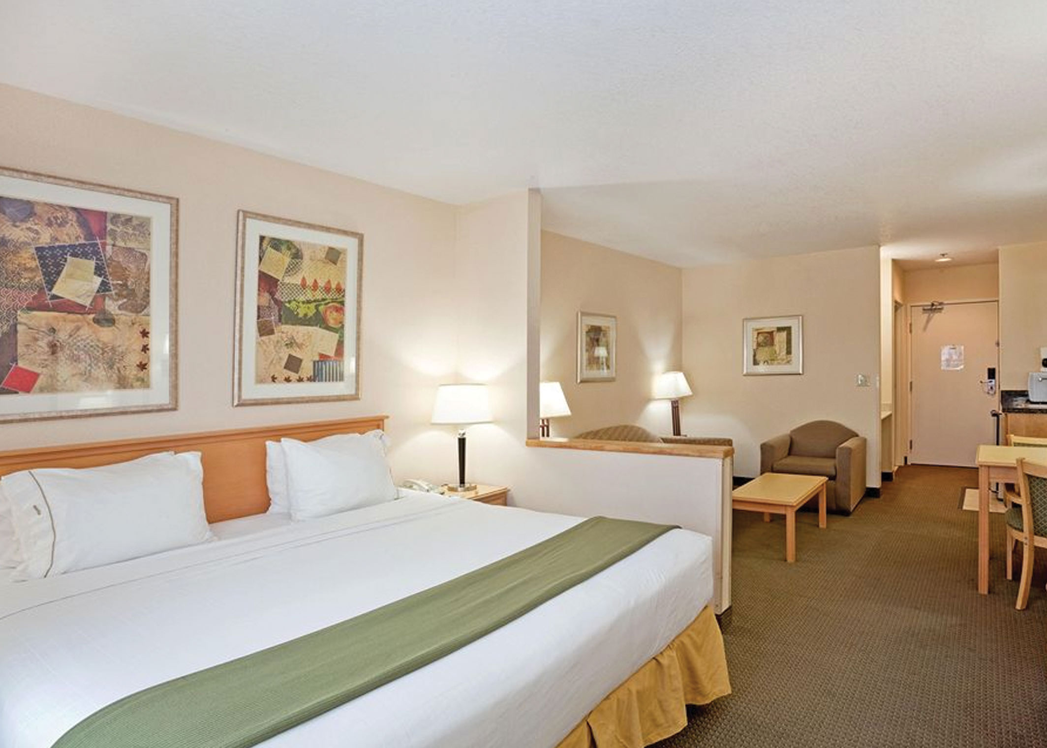 hotel room with bed, soft seating area and case goods