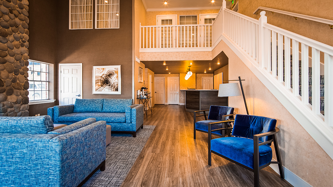 hotel lobby, white stair case, blue soft seating, dark brown reception desk, brown wall paint