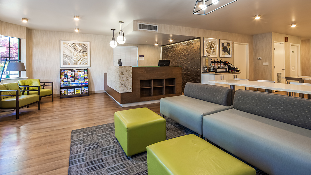 hotel lobby with gray and green soft seating, white breakfast area furniture, brown/ granite reception desk with accent wall