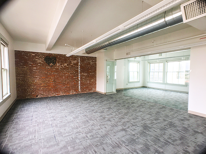 creative office space with brick walls, gray carpet tiles, exposed ceiling, conference room
