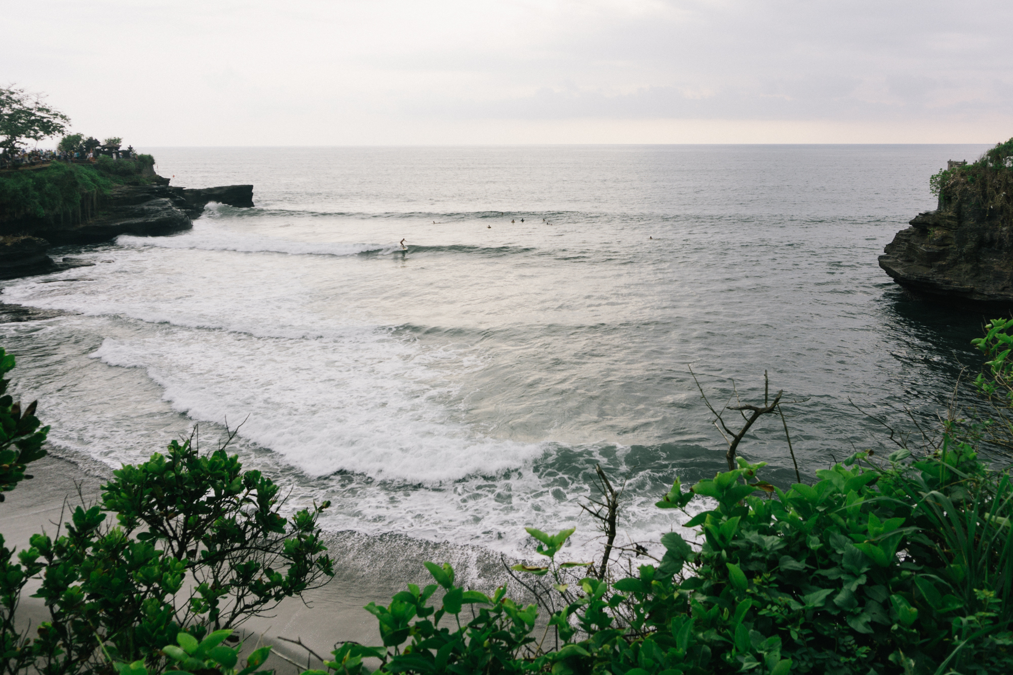 Surfers take advantage of the waves between the two temples of Tanah Lot, Bali.