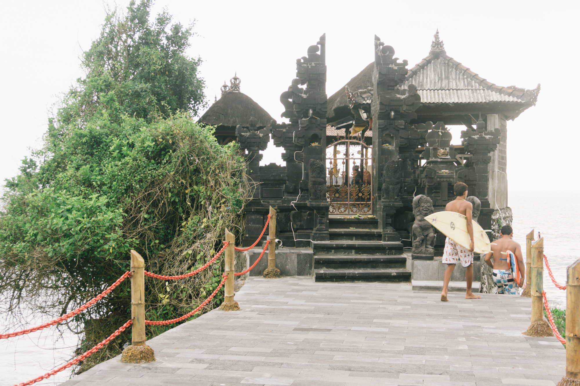 Local surfers sneak around a portion of the Tanah Lot Temple to get access to a nearby bay to surf the bay of one of the most iconic temples in Bali.