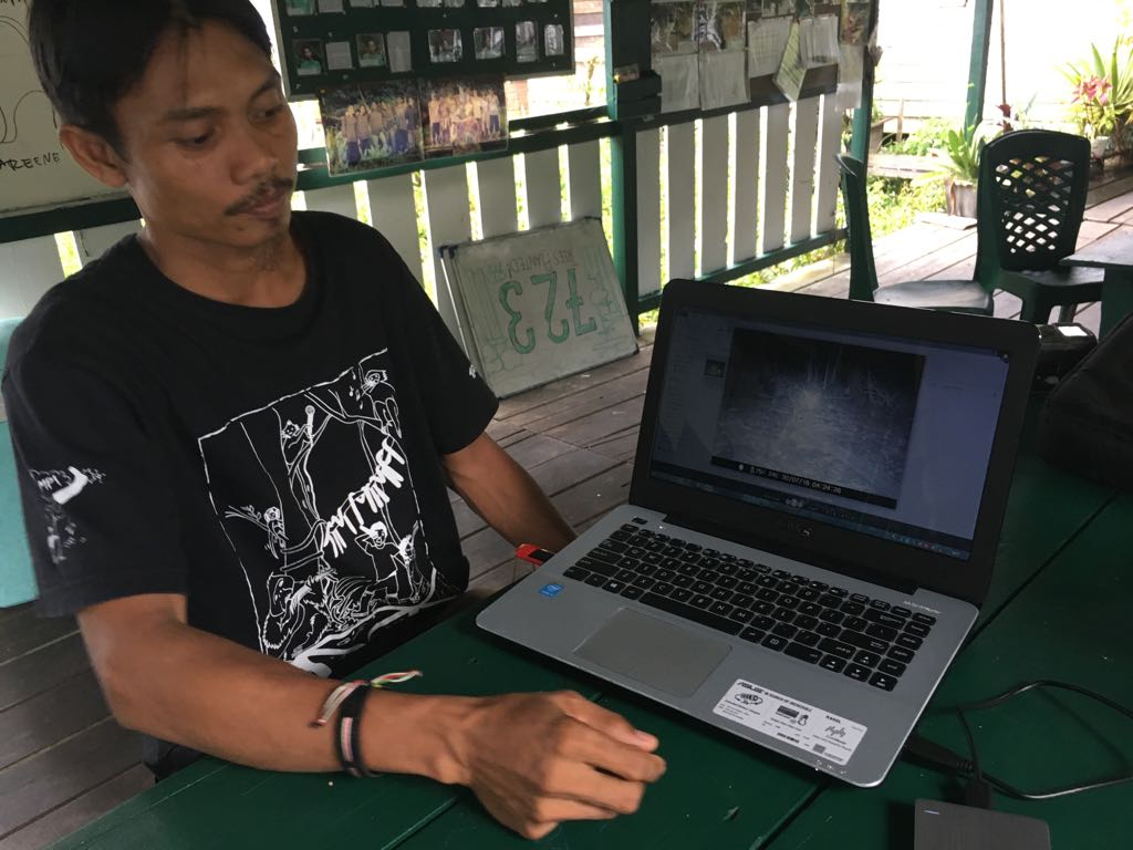Adul from BNF showing images from the camera traps in the forest.