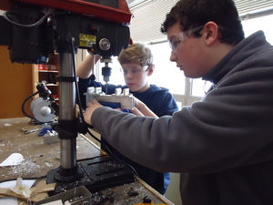 Chris and Cameron drilling the holes so we can attach the pistons to our robot.
