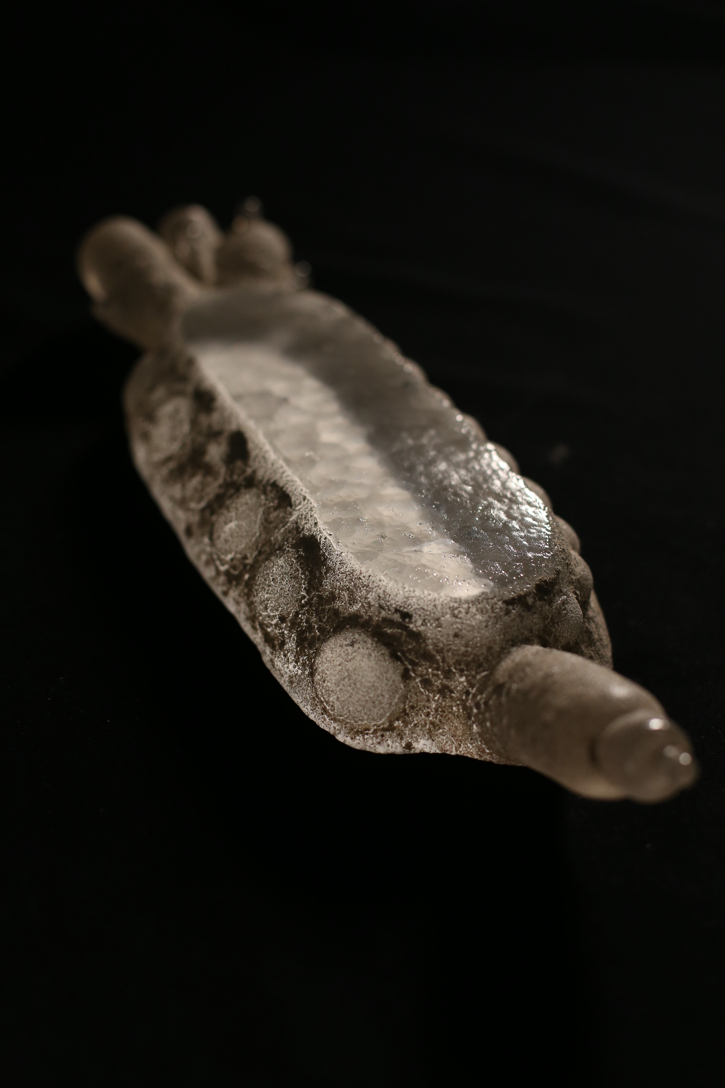 The Condensation 2014 Glass cast into a sand and graphite mold 40 x 12.7 x 7.5 cm The inspiration is surface tension and ripples. Shadows created under a calm body of water are emulated through the window.