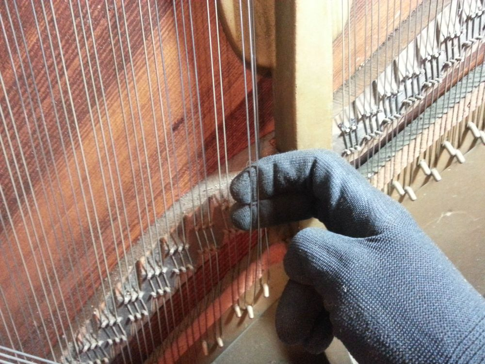Holding tension on the strings while turning the tuning pins. I wear gloves to prevent any moisture on my hands from causing the strings to rust.