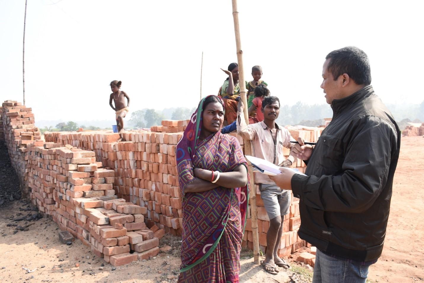 Photo 2: Evidence Action India team member, Sanjoy Yumnam talks to Guddi at the brick kiln in Jirania, West Tripura