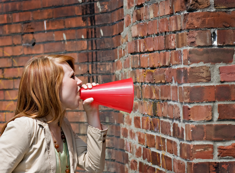Girl shouting through a megaphone at a brick wall