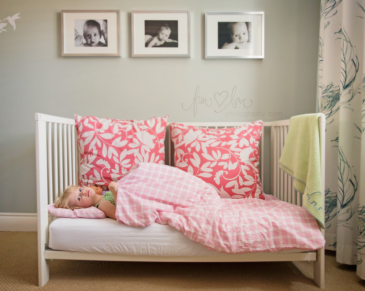 Girl in crib bed with her baby pictures on the wall