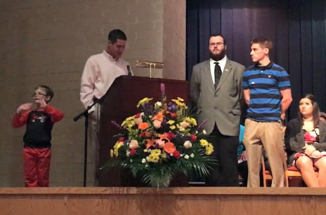 Kim's husband, Bob Hooks, and the couple's son, Talen, present scholarships to Timothy and RJ.