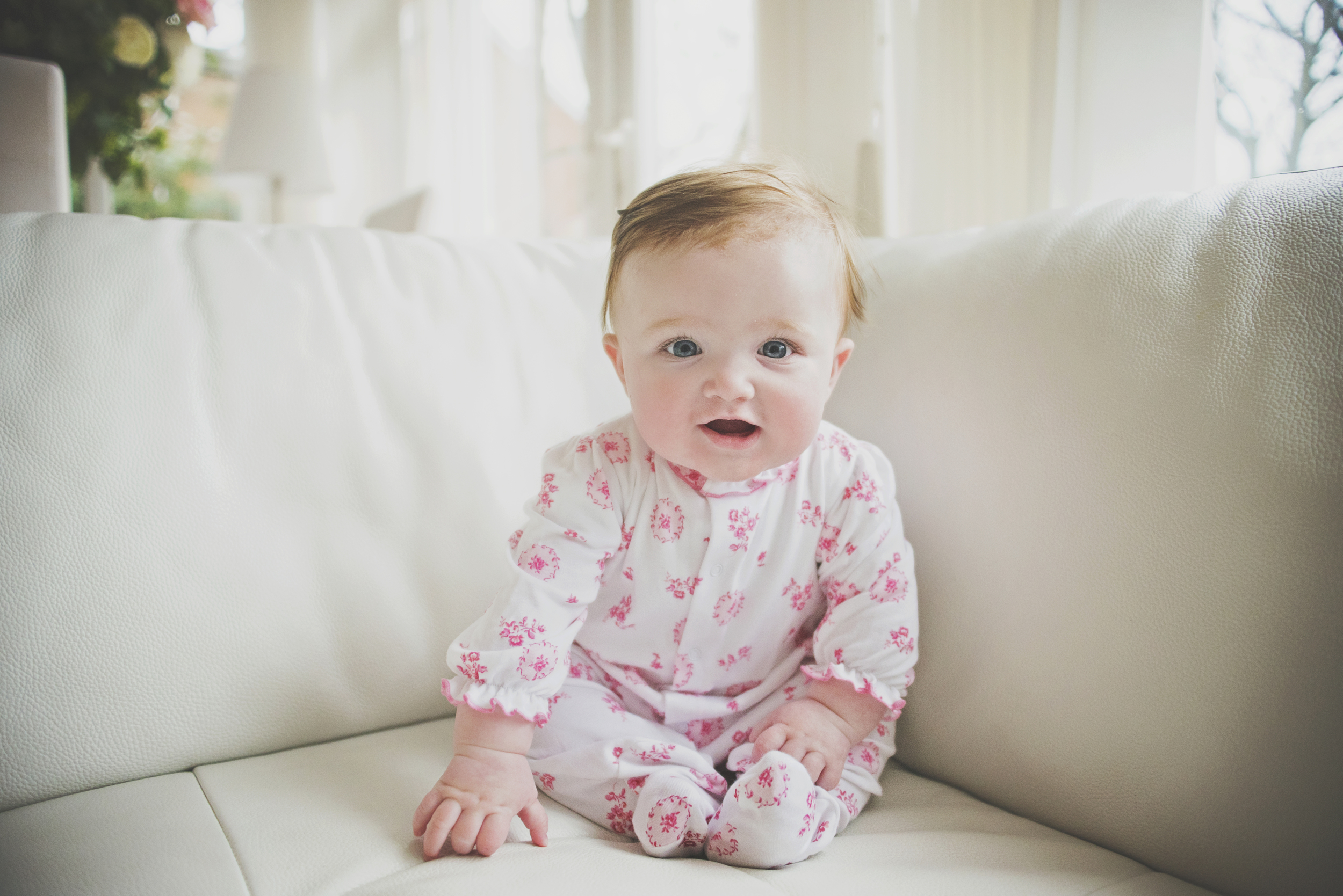 Young baby girl sits on sofa Essex Documentary and Lifestyle Portrait Photographer