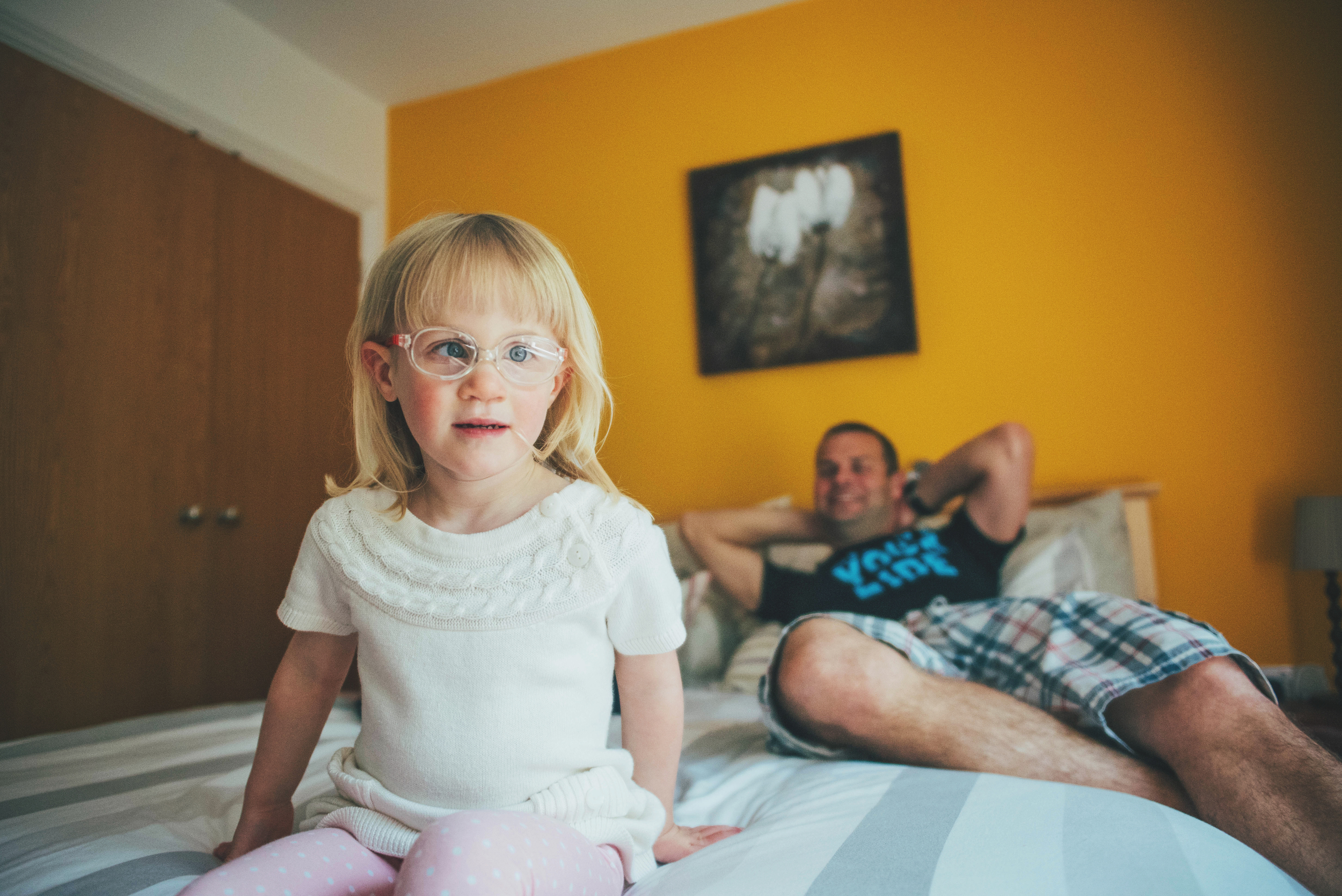 Young girl sits on bed with Dad Essex Documentary and Lifestyle Portrait Photographer