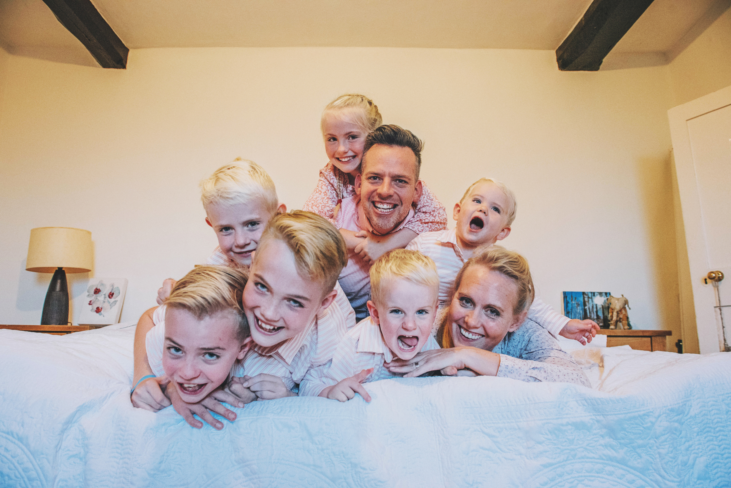 Large family cuddle on bed at home Essex Documentary and Lifestyle Photographer