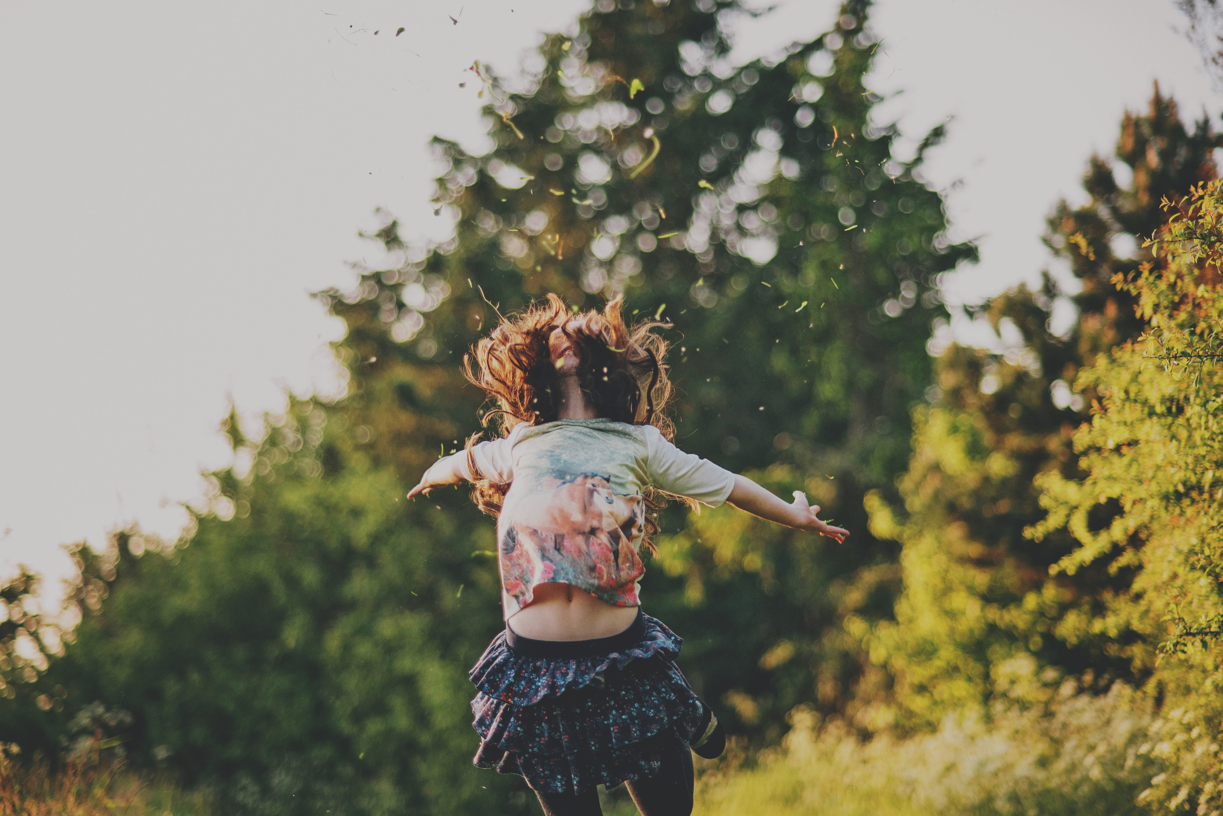 Young girl throws grass and jumps in air Documentary and Lifestyle Portrait Photographer