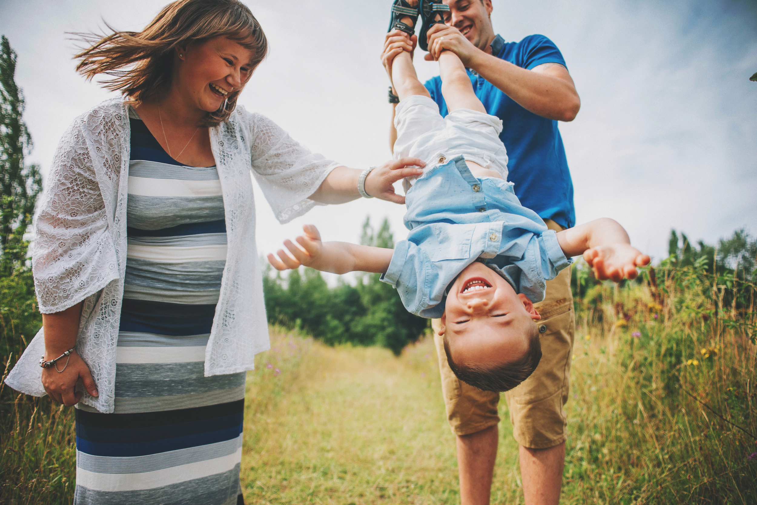 Dad and Mum laugh at upside down son Essex Documentary and Lifestyle Portrait Photographer