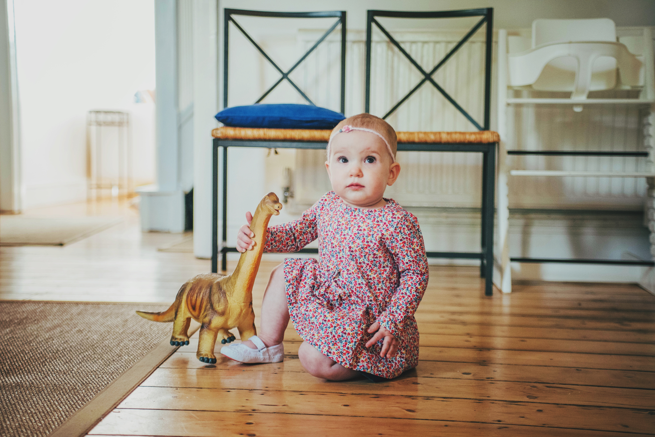 Baby girl holds dinosaur Essex Documentary and Lifestyle Photographer