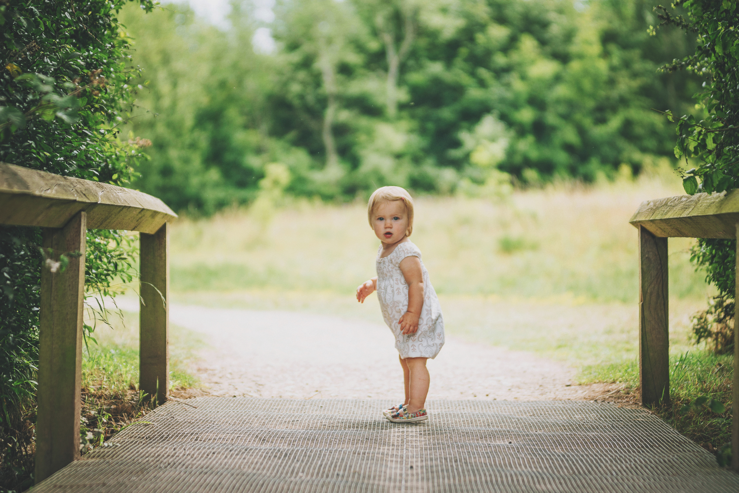 Baby girl on bridge in park Essex documentary and lifestyle portrait photographer