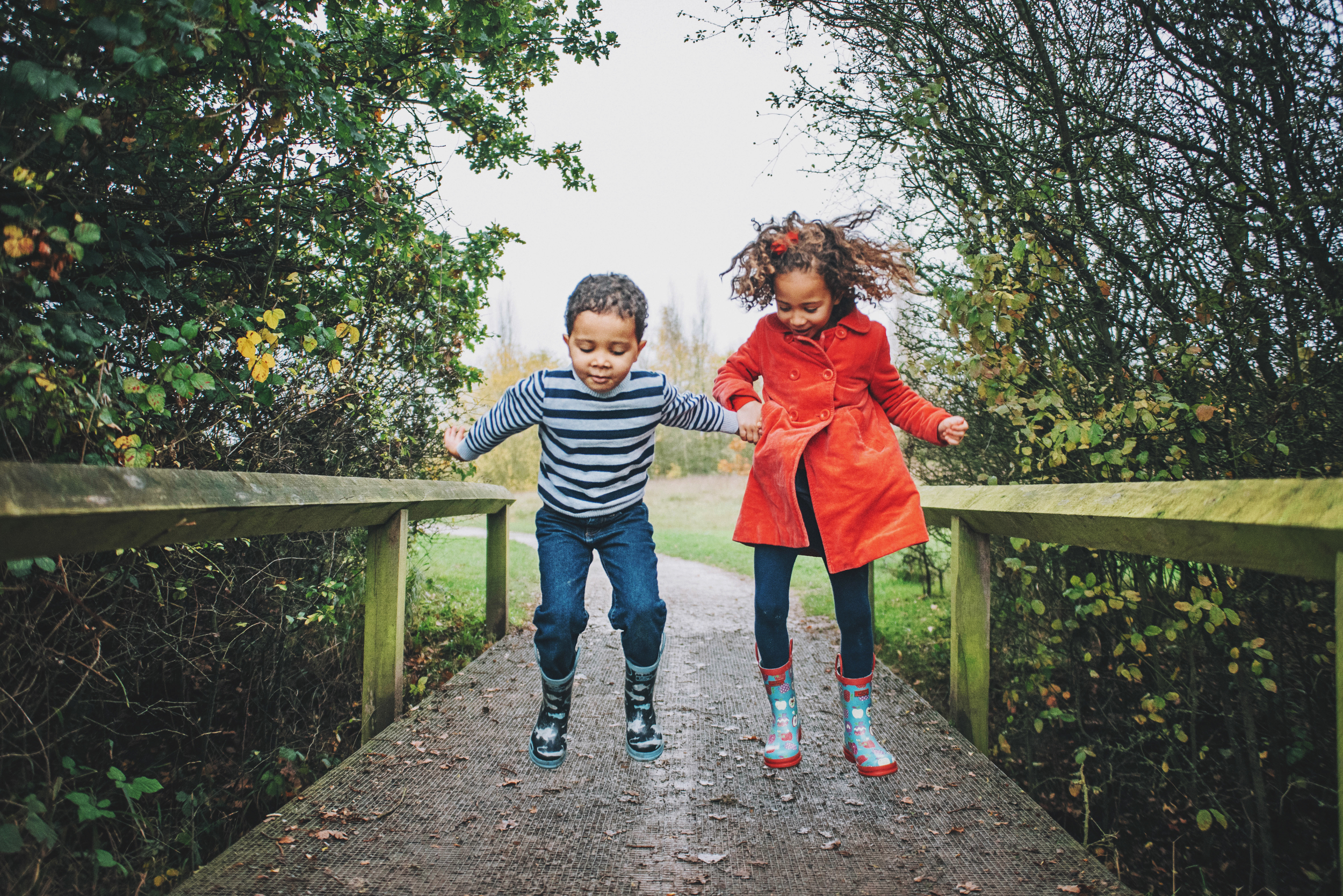 Brother and Sister jump on Bridge in wellies Essex Documentary and Lifestyle Portrait Photographer