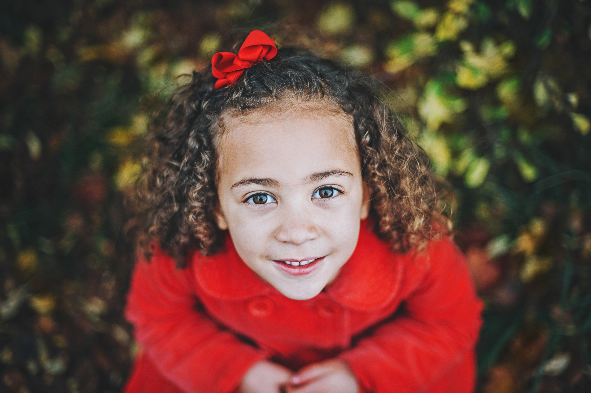 Young girl in red looks into camera Essex Documentary and Lifestyle Portrait Photographer