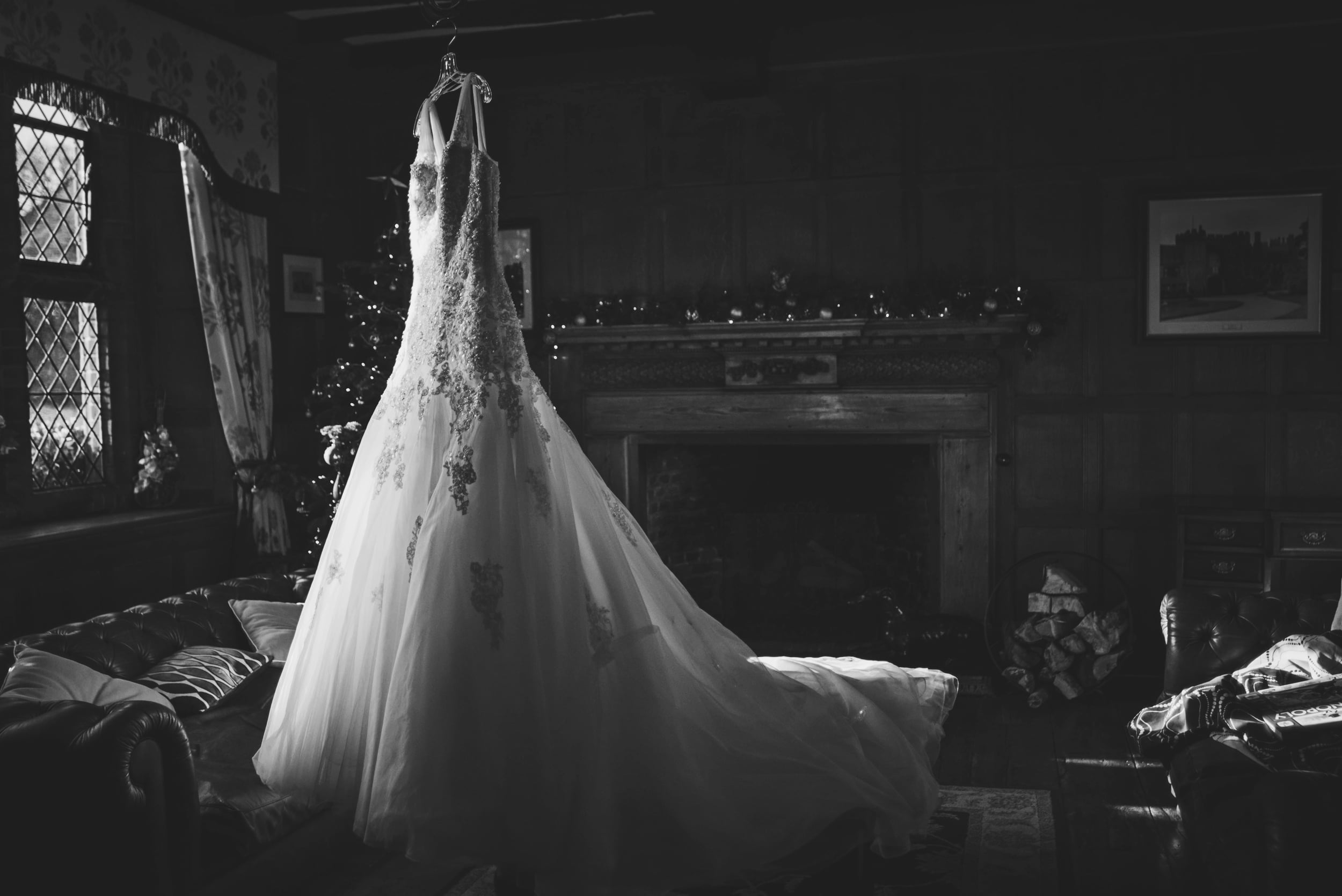 Stunning dress hangs in sitting room Leez Priory Christmas Essex UK Documentary Wedding Photographer