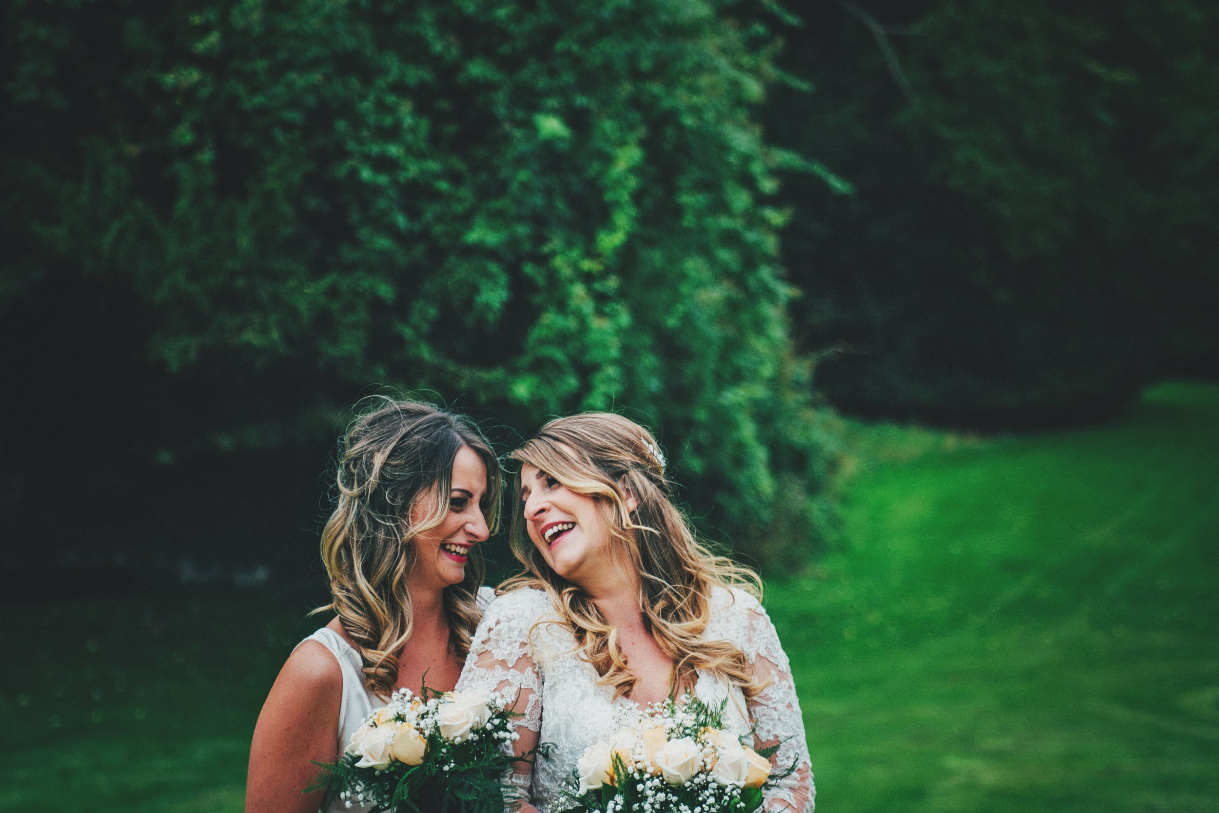 Bride laughs with sister Rustic Essex UK Documentary Wedding Photographer