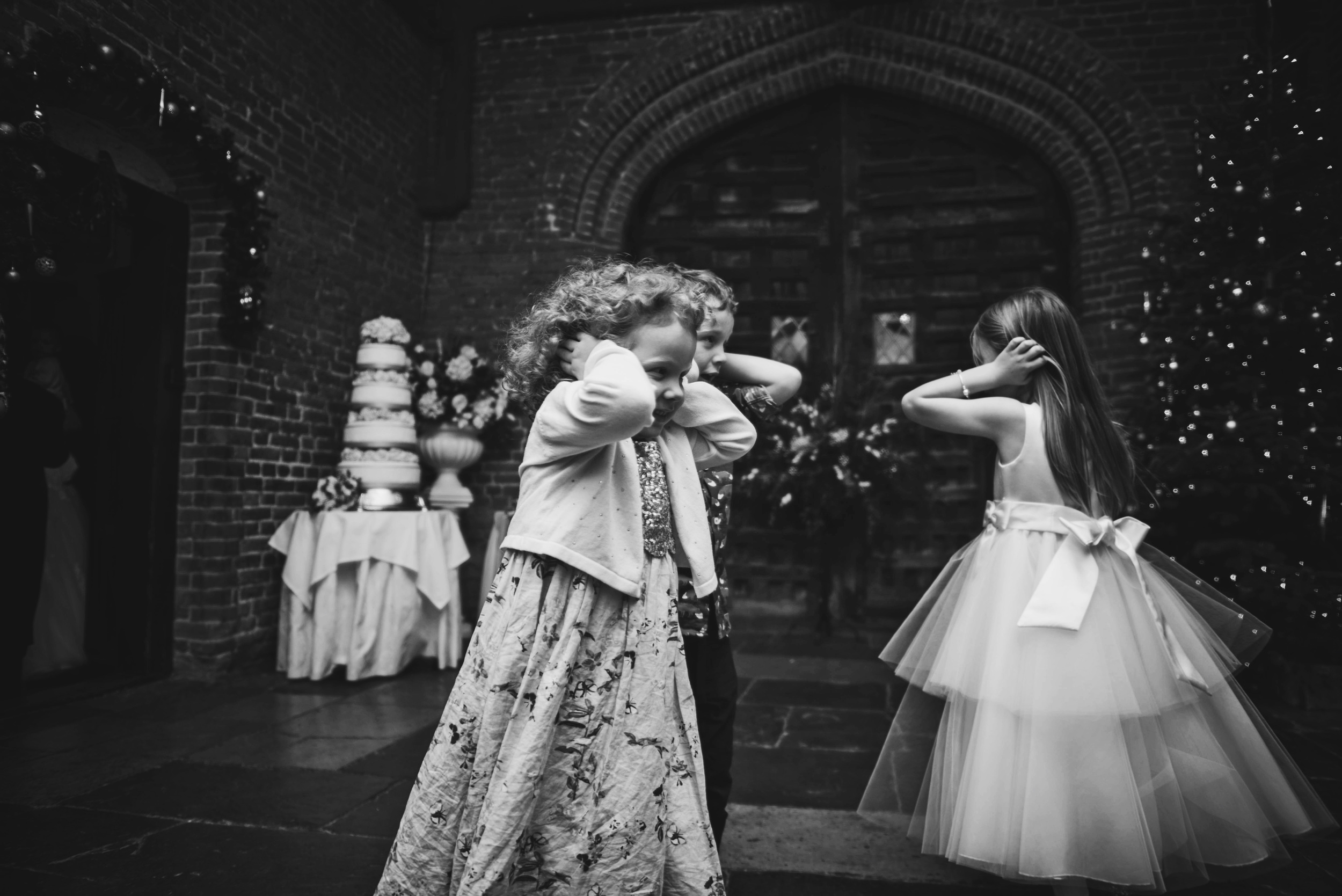 Little girls cover ears for wedding singer Christmas Leez Priory Essex UK Documentary Wedding Photographer