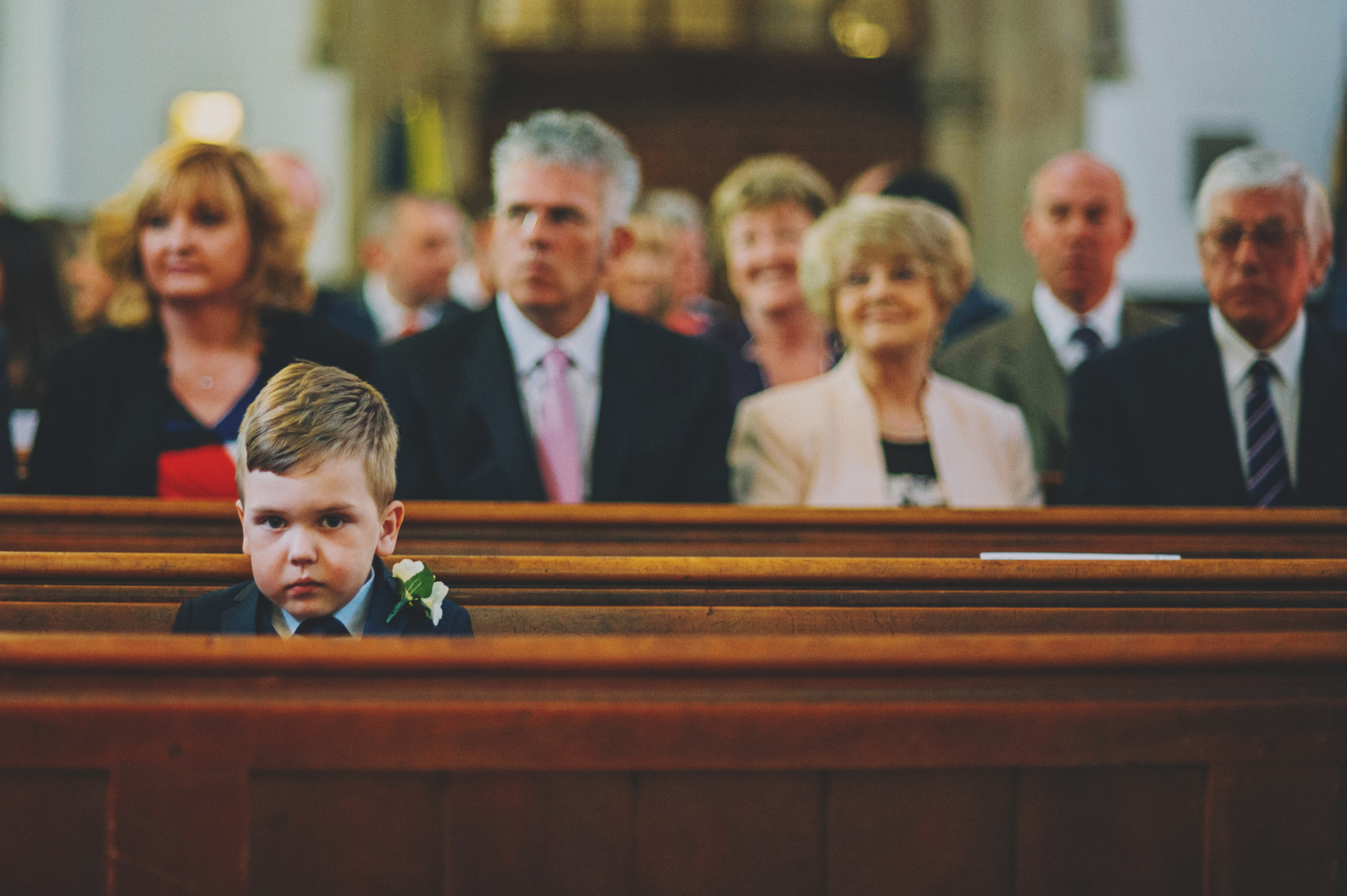 Grumpy page boy in church Rustic Blake Hall Essex UK Documentary Wedding Photographer